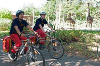 Zwei FSJler fahren auf Fahrrädern durch den Kölner Zoo